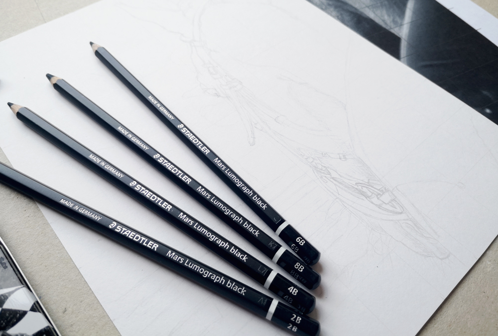 A variety of Staedtler Mars Lumograph Black pencils used to draw a blurred background of a Horse drawing.